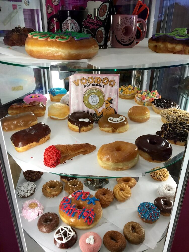 Tiers of many different kinds of colorful donuts at Voodoo Doughnuts