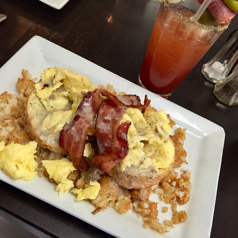 Biscuits, eggs, hash brows, gravy, and bacon with a bloody mary