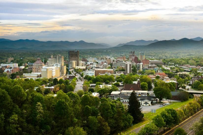 skyline of asheville nc buildings poking up between hills and trees