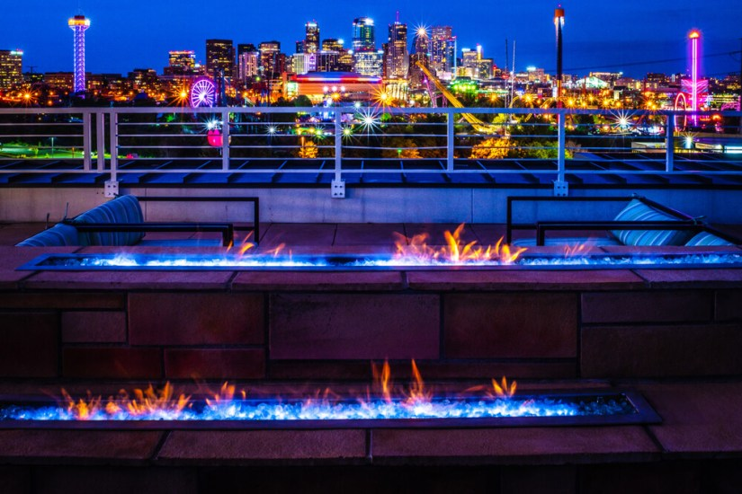 colorful view of denver at night with lit up fire pits and city colors