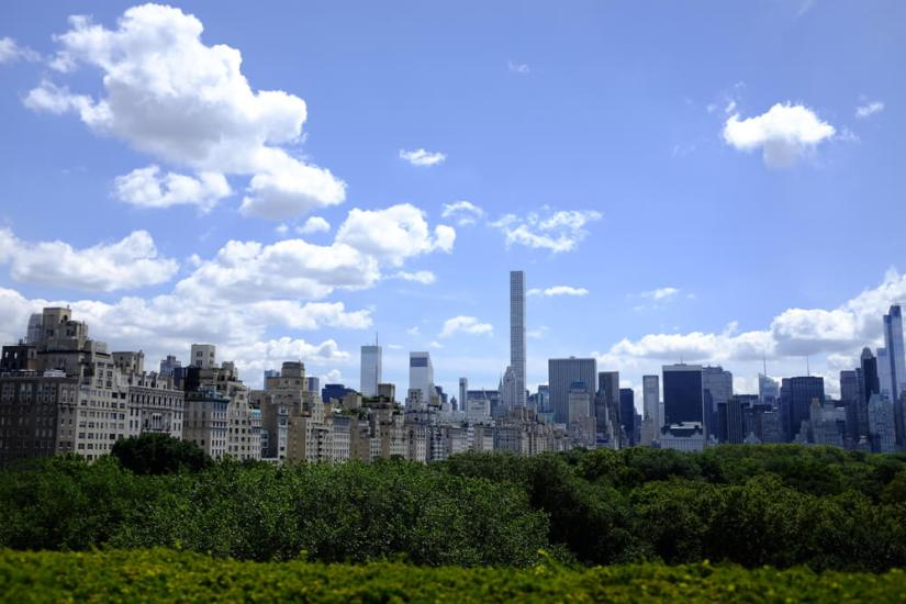 View of greenery of Central Park from the Met rooftop with skyscrapers behind it