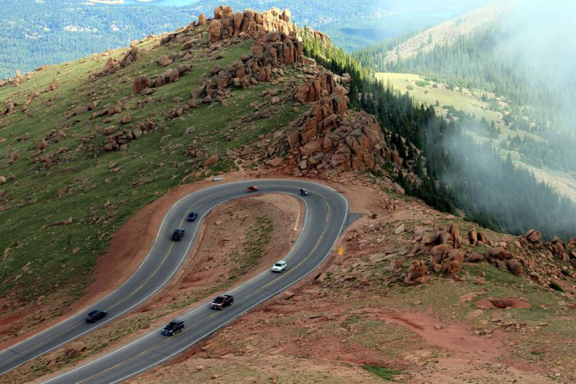 Hairpin curve in the mountains with several cars going up the mountain and some light fog, on a popular Colorado road trip