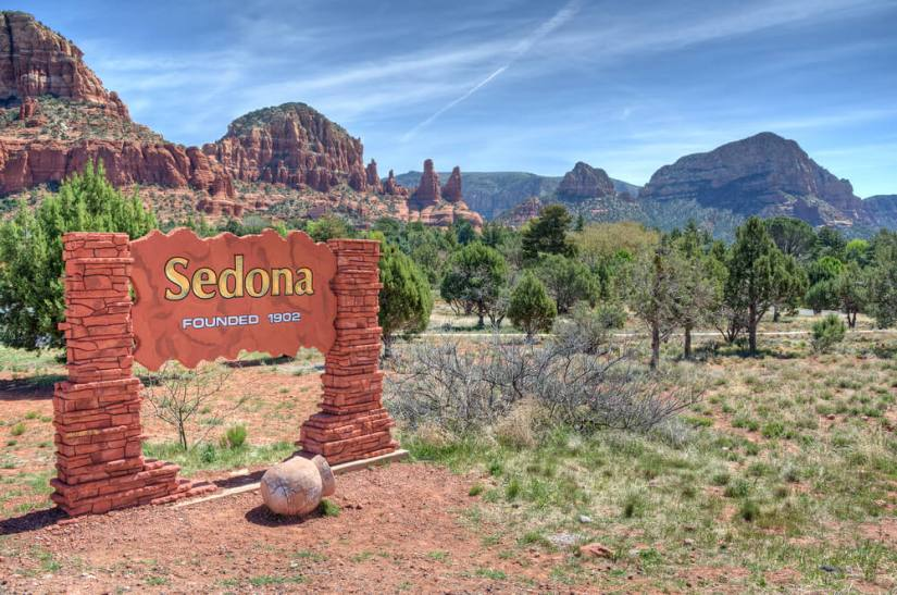 """Sign that reads """"Sedona founded 1902"""" with red rock formations and trees in the foreground of the photo"""