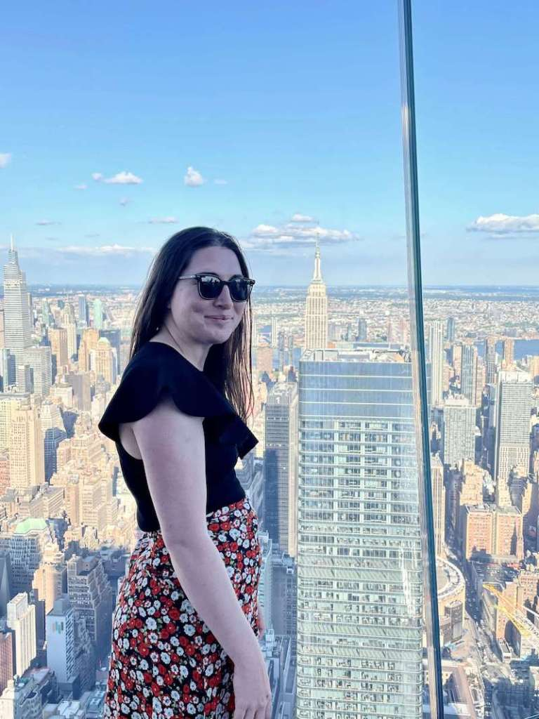 Allison Green smiling with a view of the Empire State Building behind her while visiting The Edge observation deck in Manhattan