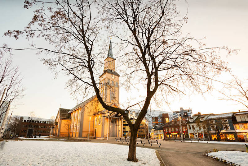 Brownish-tan wooden cathedral in a square in Tromso Norway in winter with snow on the ground and buildings lit up in evening