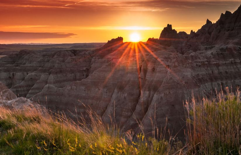 Sunset over the Badlands of South Dakota with a sunburst effect and grass in the foreground