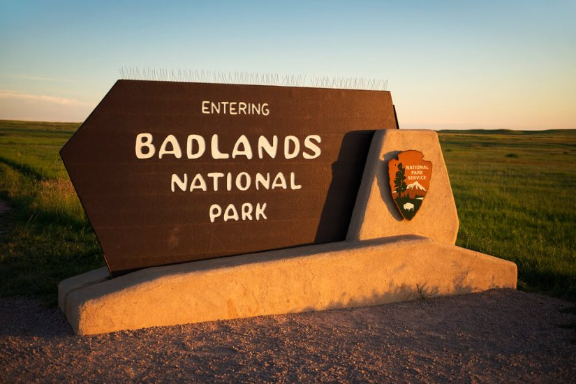 """NPS Sign reading """"Entering Badlands National Park"""" in the late afternoon sunset light"""