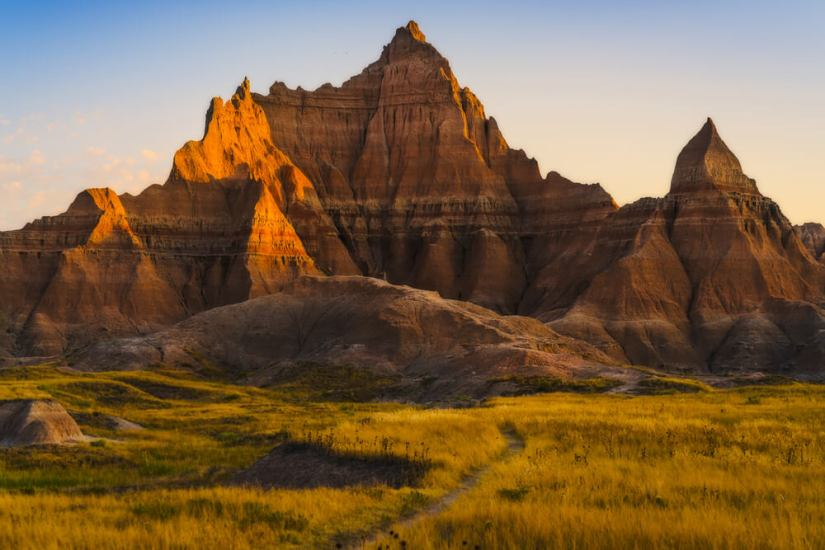 One of the many pointed rock formations of Badlands National Park with sunset light making shadows