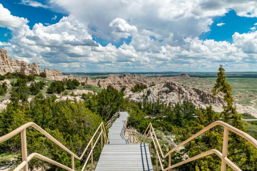 Stair trail boardwalk leading to beautiful rock formations amidst a green lush landscape in the Badlands