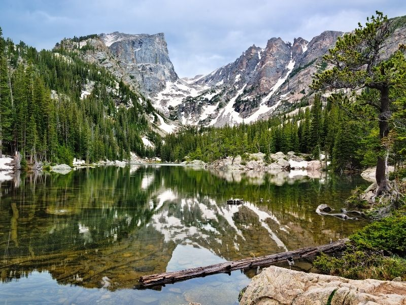 Hiking in Rocky Mountain National Park at the beautiful Dream Lake with still, glassy water reflecting trees and snow-dotted mountain peaks