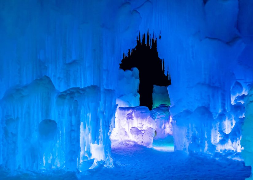 Ice Castles lit up at night with blue light and icicles