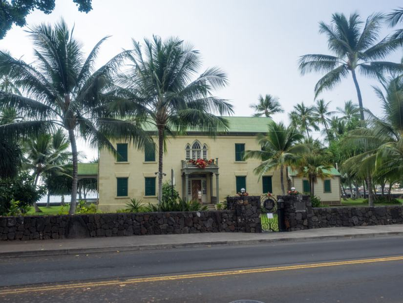 yellow toned historic building of hulihee palace on the road with palm trees in front of the ocean