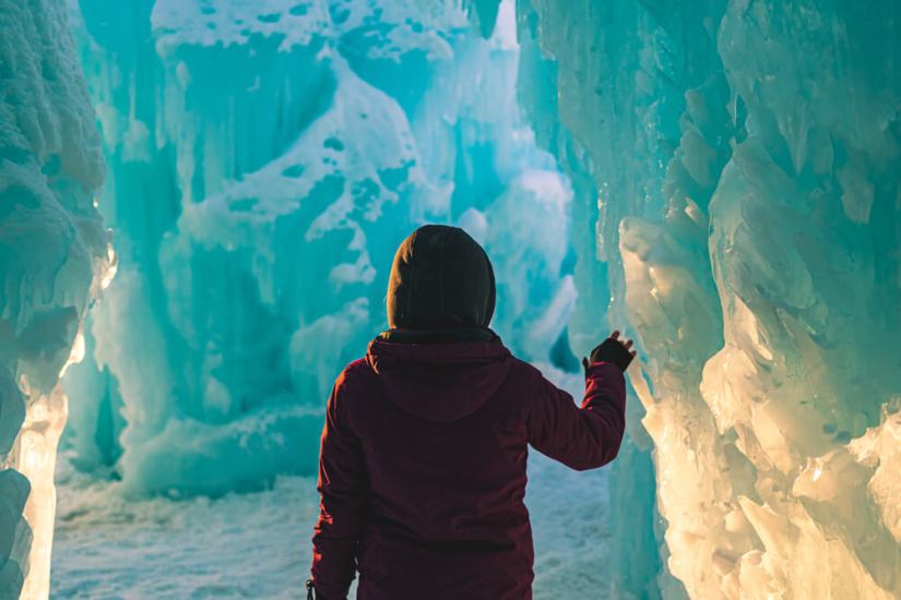Person wearing a jacket and gloves while visiting the Dillon Ice Castles