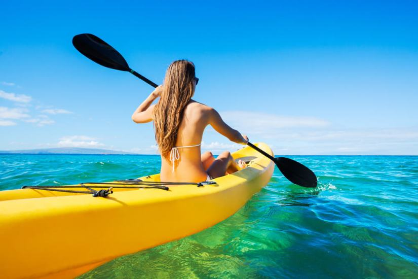 woman kayaking in a yellow kayak on brilliant clear water