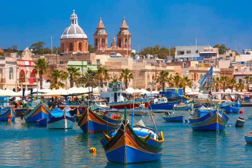 Colorful boats in a harbor in Malta with architecture behind
