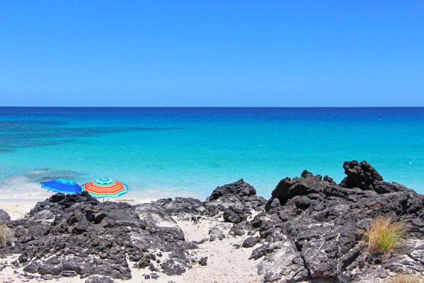 two colorful beach umbrellas behind black lava rock with beautiful turquoise sea and white sand in the background