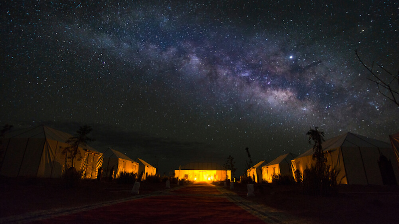 Tents for camping in the Sahara Desert at night, lit up by a fire or lantern, with the Milky Way overhead