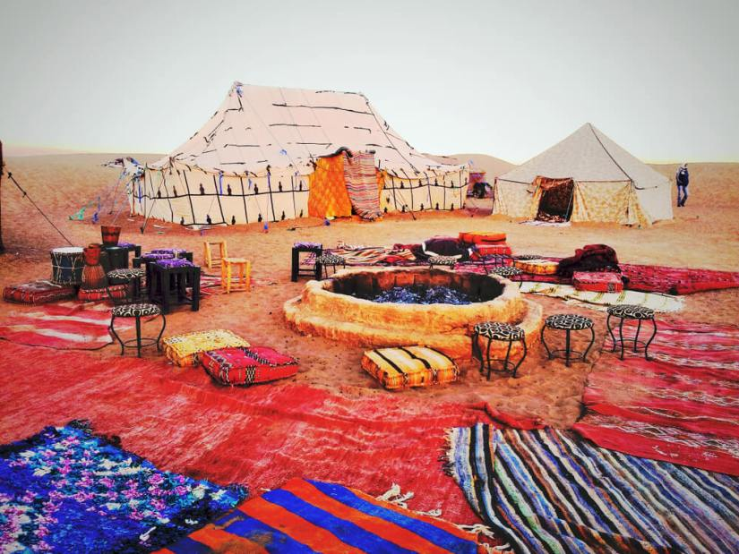 rugs surrounding a campfire and some makeshift tents in the Sahara