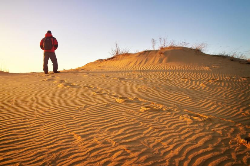 Man wearing winter clothes standing in the Sahara dunes