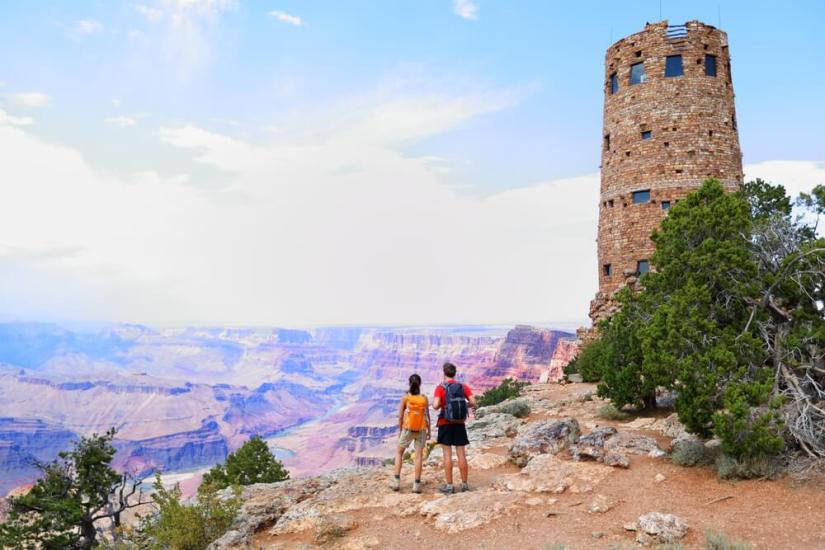 a brick-style watchtower towering over the south rim of the grand canyon; a couple wearing backpacks looking over the canyon off in the distance