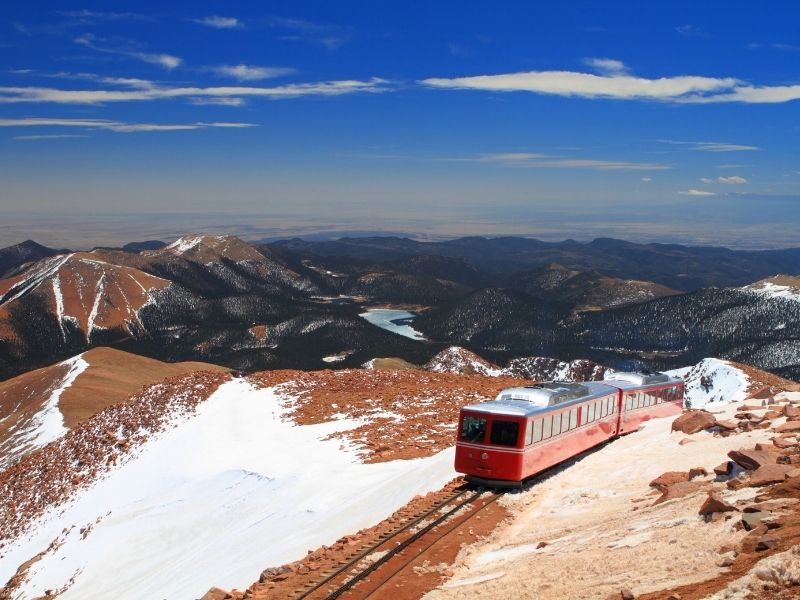 famous red railway car with a silver roof ascending pikes peak with view of mountains with light dusting of snow in the distant background