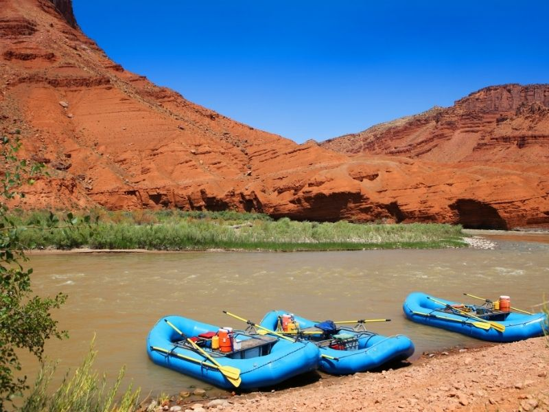 Three blue rafts sitting in the Colorado River in Moab near red rocks