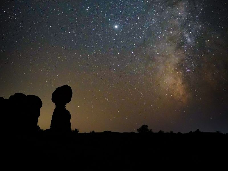 Stargazing in Moab, Utah with the milky way visible as well as balanced rock silhouetted against the night sky in arches national park