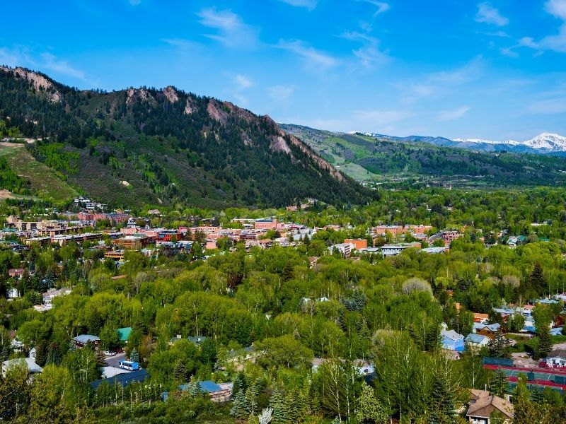 The green trees of Aspen Colorado and houses in the town below in the mountains