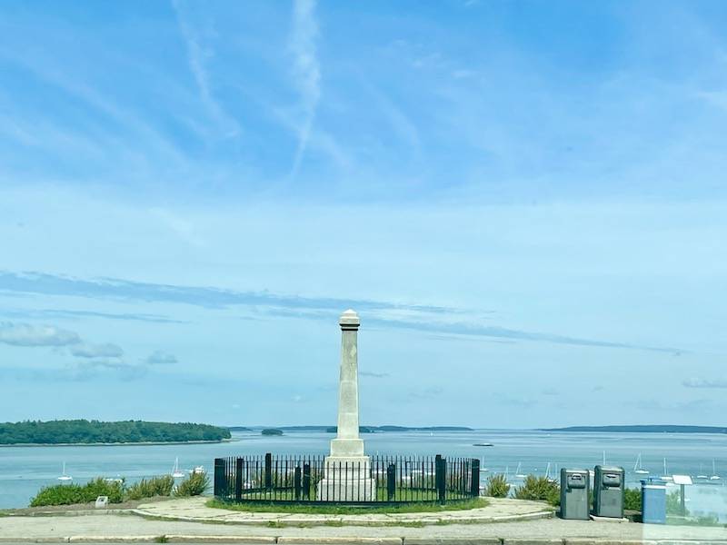 a pillar memorial in front of the water and islands at the edge of portland
