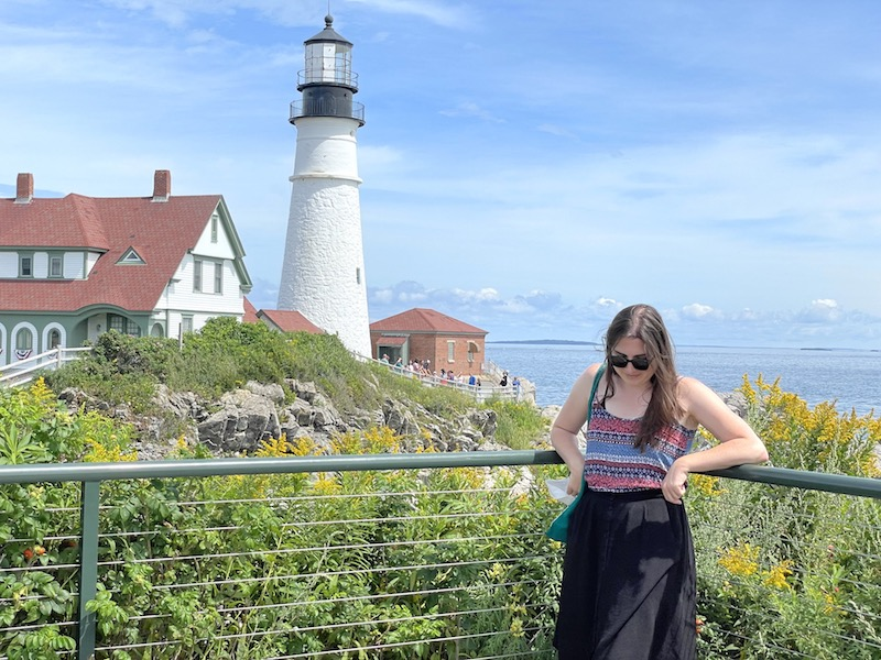 allison standing in front of portland head light house on a sunny day in summer