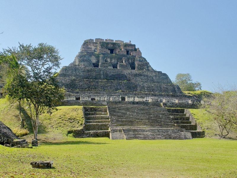 the largest stone structure at xunantunich surrounded by grass, trees, etc