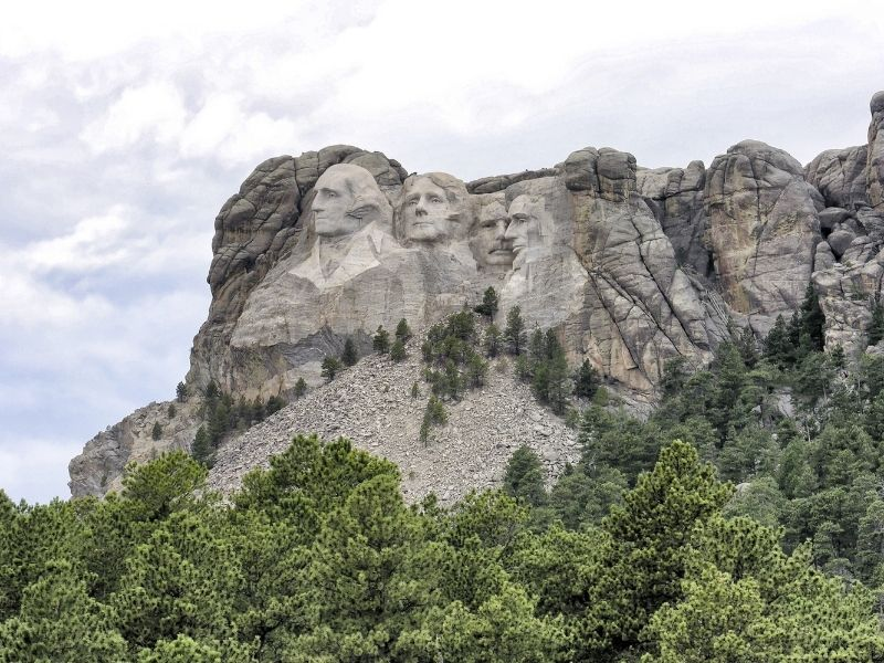 A further away view of the four faces of Mt Rushmore so that you can see the scale of the sculpture against mountain and trees