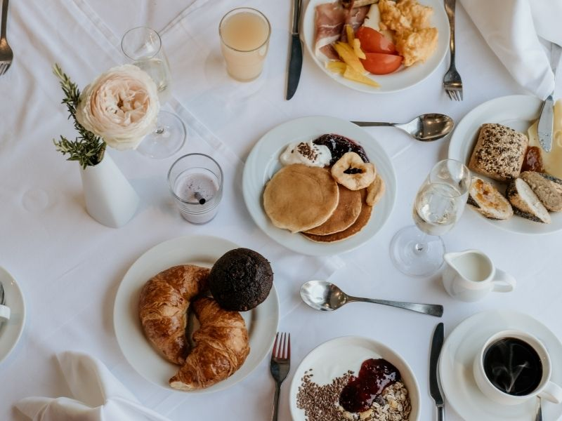 a breakfast spread on a white tablecloth with pastries and coffee and pancakes