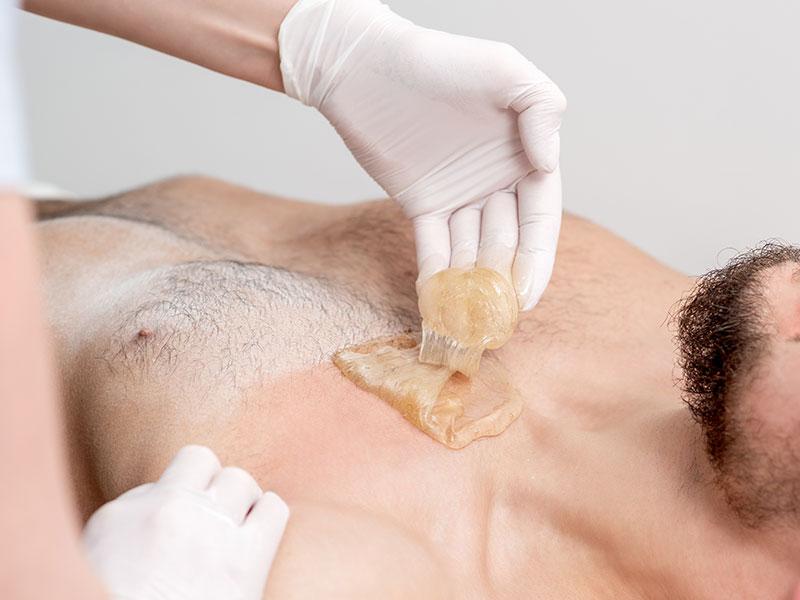 Men Getting Body Sugaring Treatment