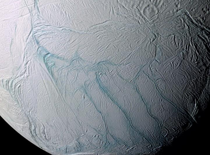 Enceladus possui água líquida e por essa razão é um forte canditado na busca pela vida extra-terrestre. No quadrante inferior-direito da imagem aparecem as quatro grandes listras de tigre, destacadas na cor azul. {5}