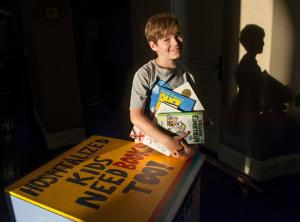 Ethan Posner, 9,  was diagnosed with acute lymphoblastic leukemia in 2014 and found reading to be great solace while hospitalized at CHOC.  Ethan started both a lending and gifting  library at CHOC called Ethan and Choco's Book Club. The family has collected over 6,000 books. He also does daily short video book reviews on YouTube and continues his cancer treatment.  Posner with a donation box built by his father. Photo taken on  Monday, November 7, 21016.  (Photo by Ana Venegas, Orange County Register/SCNG)