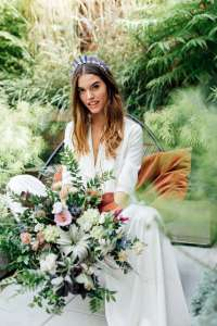 A beautiful model bride poses at a styled ethical weddings shoot, featuring eco friendly wedding style and organic wedding florals.
