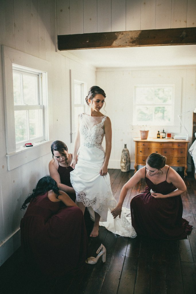 bridesmaids helping the bride put on her shoes
