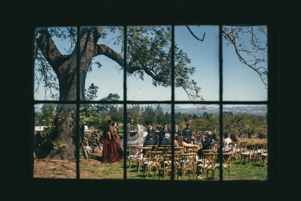 view of wedding ceremony as viewed through a window