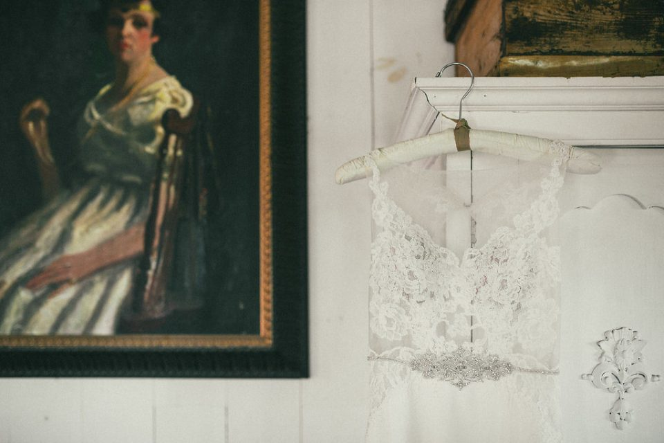 detail shot of bride's gown hung over the corner of a dresser