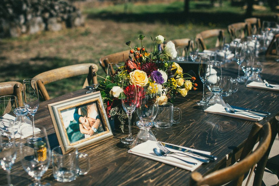 wedding party table set with flowers, utensils, and photographs