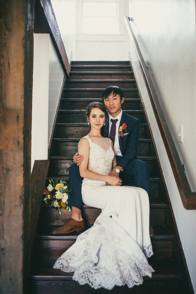 Bride and groom sitting on steps of stairs inside house