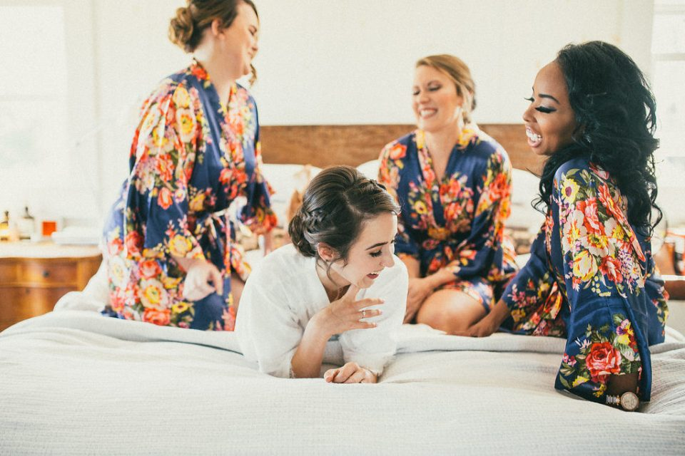 bride laying on bed, surrounding by her bridesmaids