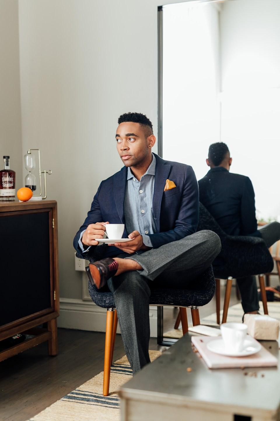 ethically dressed man in suit, sits holding coffee