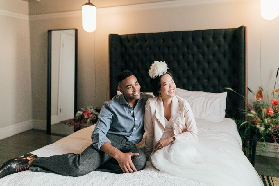 Ethically styled couple sitting on bed