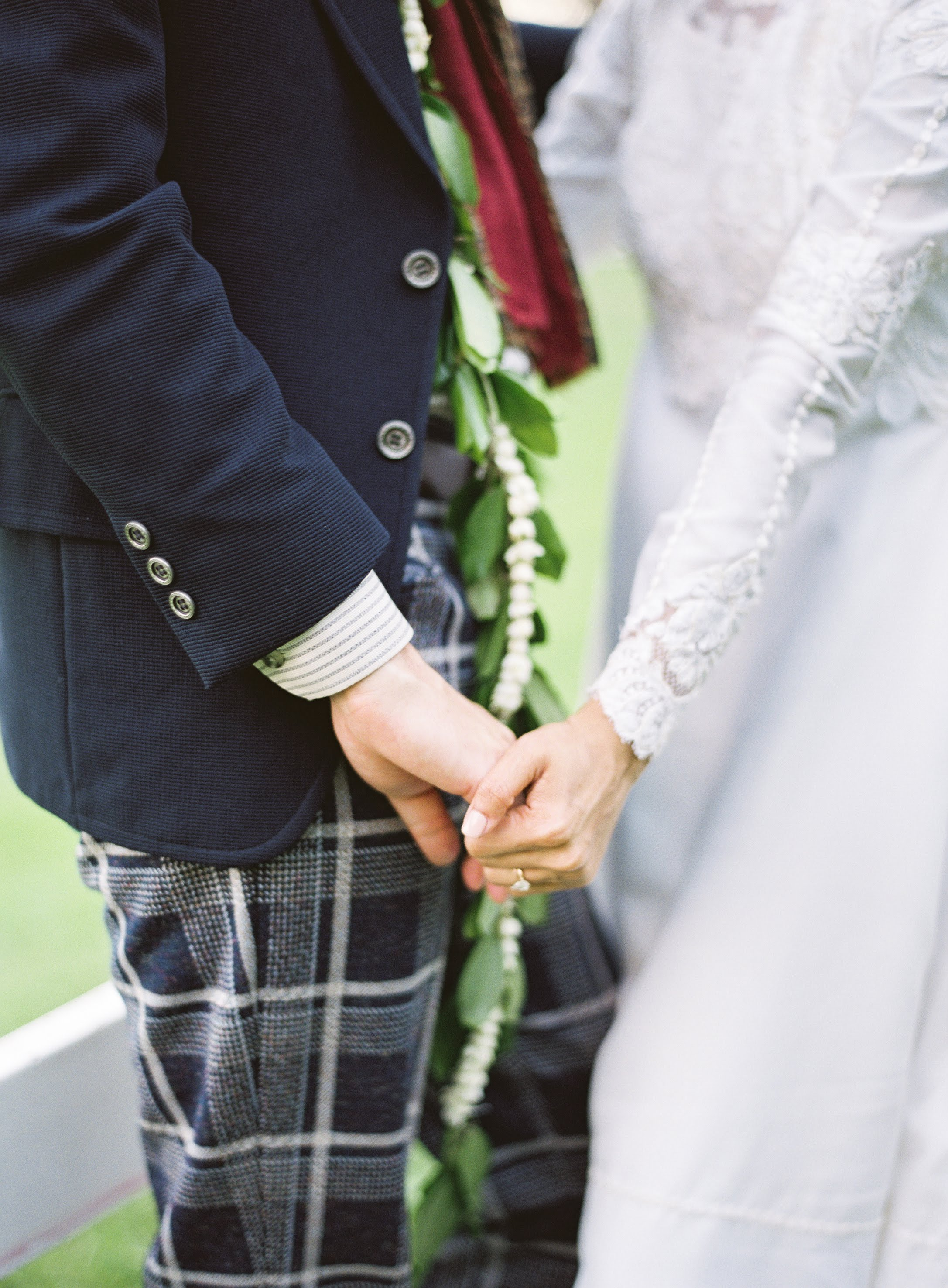 Up close of bride and groom holding hands