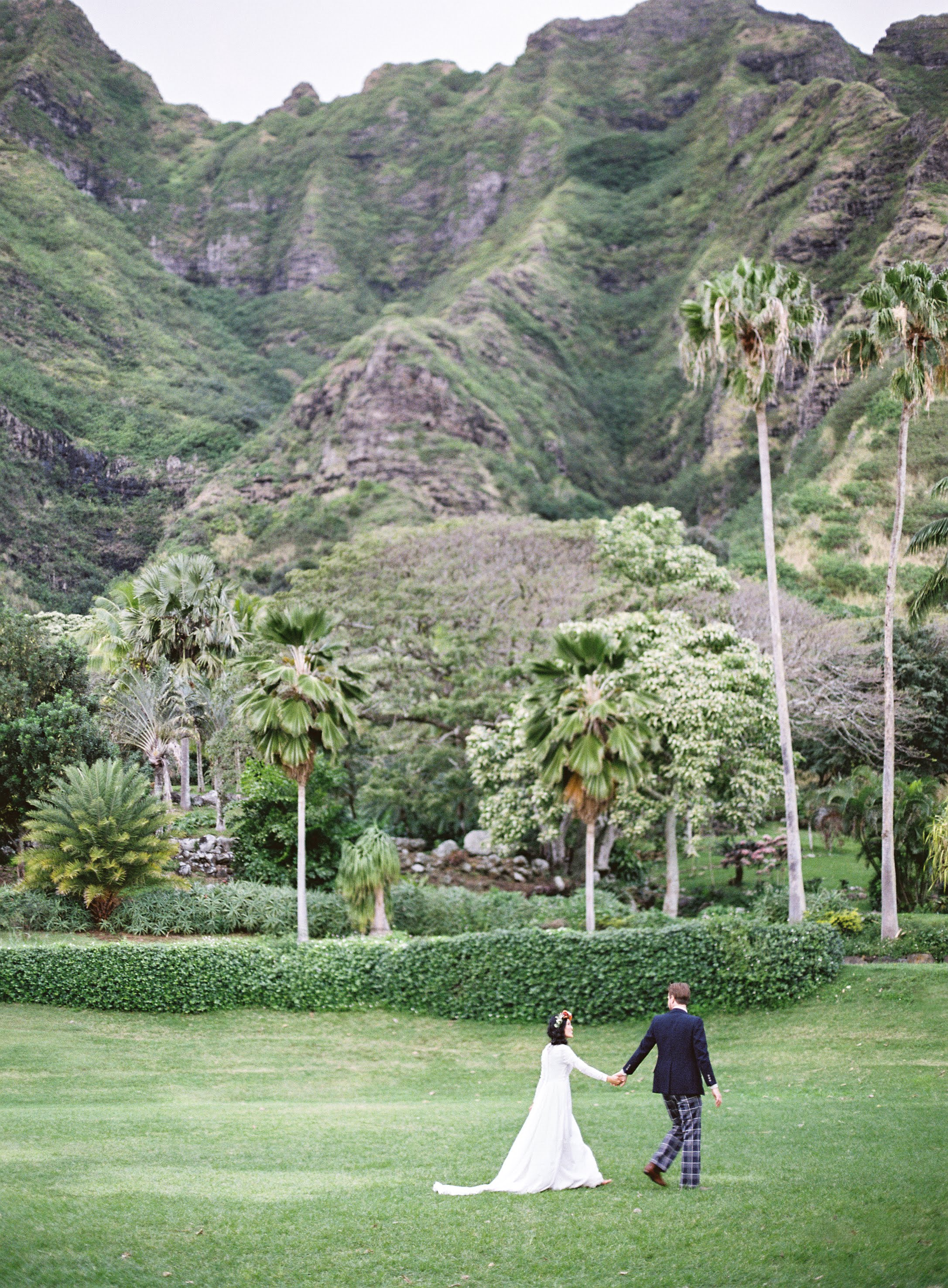 Bride and froom hold hands, walking through greenery