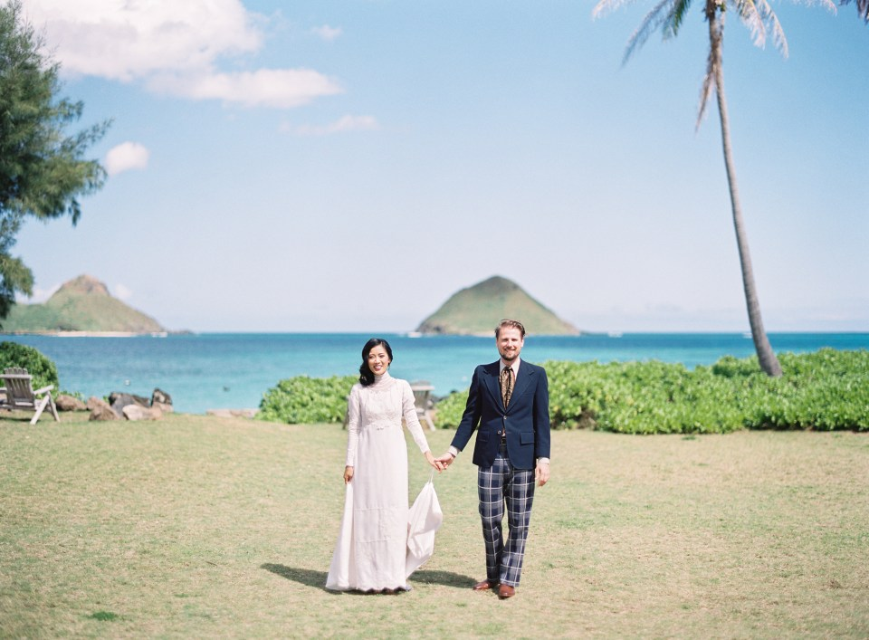 Bride and groom stand holding hands in front of beach background