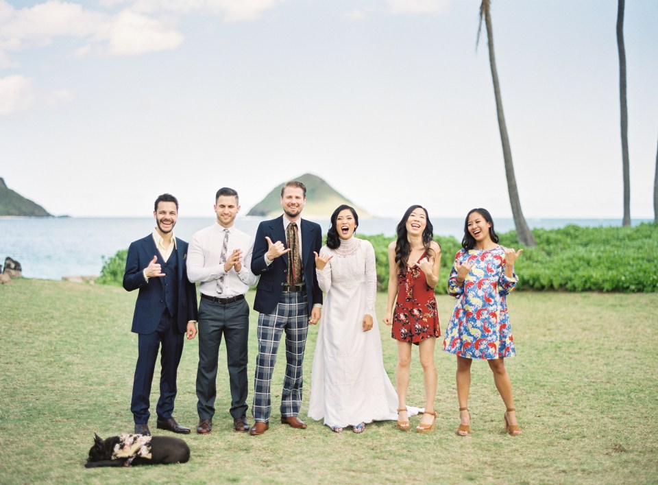 Bride and groom stand with family in front of beach