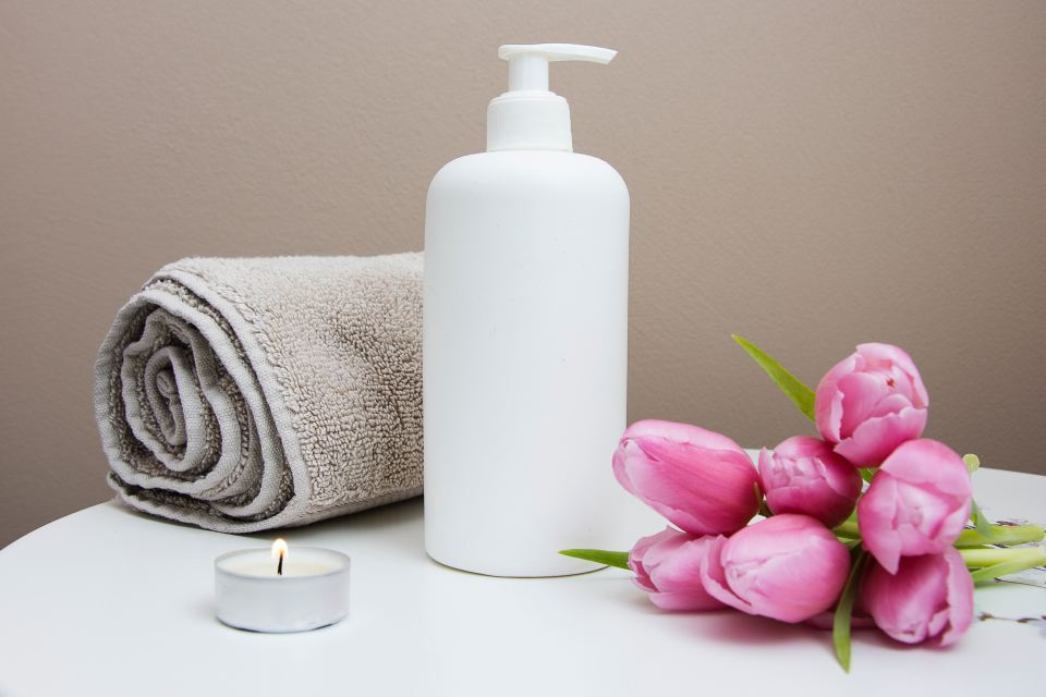 Collection of spa items: towel, lotion, flowers, candles